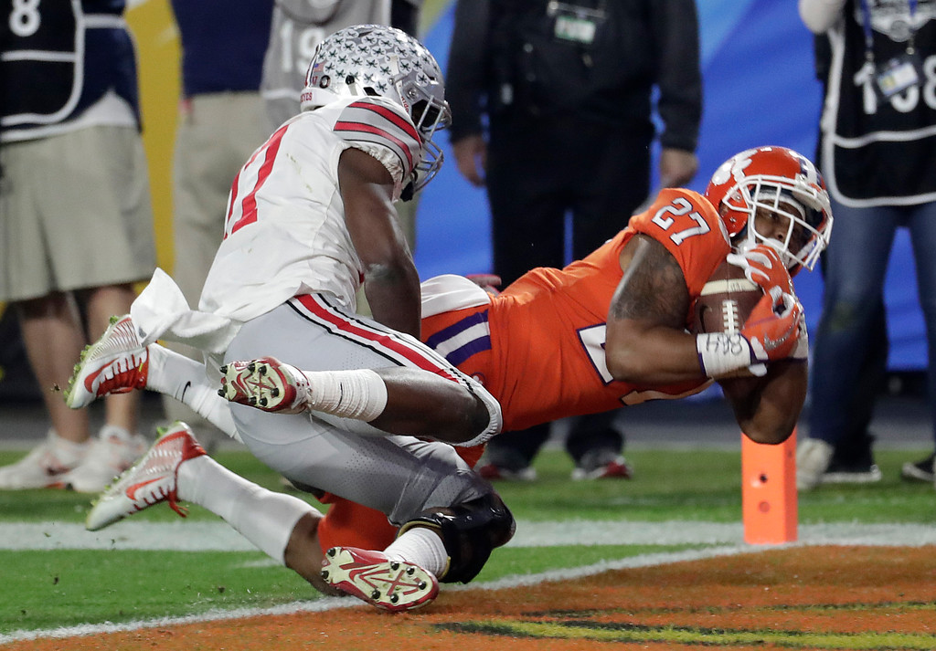 . Clemson running back C.J. Fuller (27) pulls in a touchdown pass as Ohio State cornerback C.J. Saunders (17) defends during the first half of the Fiesta Bowl NCAA college football game, Saturday, Dec. 31, 2016, in Glendale, Ariz. (AP Photo/Rick Scuteri)