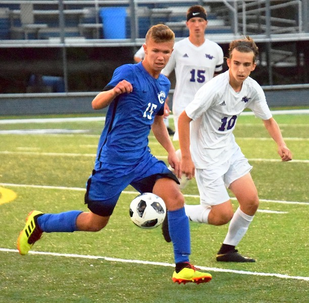 Zach Pier (15) of host Gibraltar Carlson is defended by Woodhaven's Gio Covelli (10) during Wednesday night's Downriver League match. The Marauders ultimately fell by a score of 3-2 and wrapped up the first half of Downriver League play in third place. Alex Muller - For Digital First Media