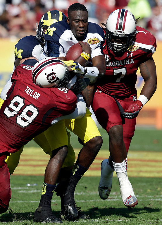 . Michigan quarterback Devin Gardner (12) loses his helmet as he is hit by South Carolina defensive ends Devin Taylor (98) and Jadeveon Clowney (7) during the second quarter of the Outback Bowl NCAA college football game, Tuesday, Jan. 1, 2013, in Tampa, Fla. (AP Photo/Chris O\'Meara)