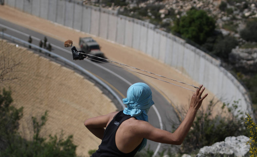 Description of . A Palestinian youth readies to sling a stone at Israeli  soldiers as they patrol along the controversial Israeli built separation barrier during clashes close to the village of Bilin, just west of the city Ramallah, in the occupied Israeli West Bank, on April 13, 2012. AFP PHOTO/ABBAS MOMANI/AFP/Getty Images