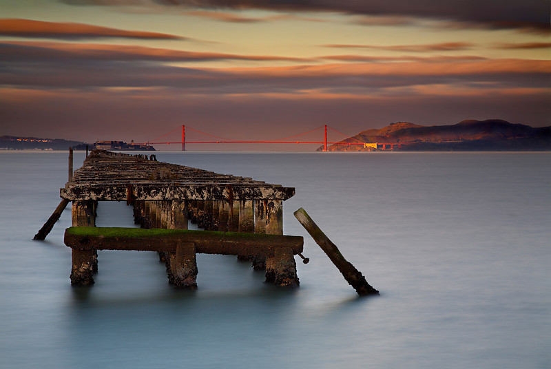 Image #2 of the Berkeley Pier. The sun came though an opening in the clouds, spotlighting the bridge and hills. Alcatraz island is at the end of the pier.  A long exposure was used (hence the dark ND 8 filter and F22), in order to soften the chaotic water so as not to distract from the main elements of the photograph.