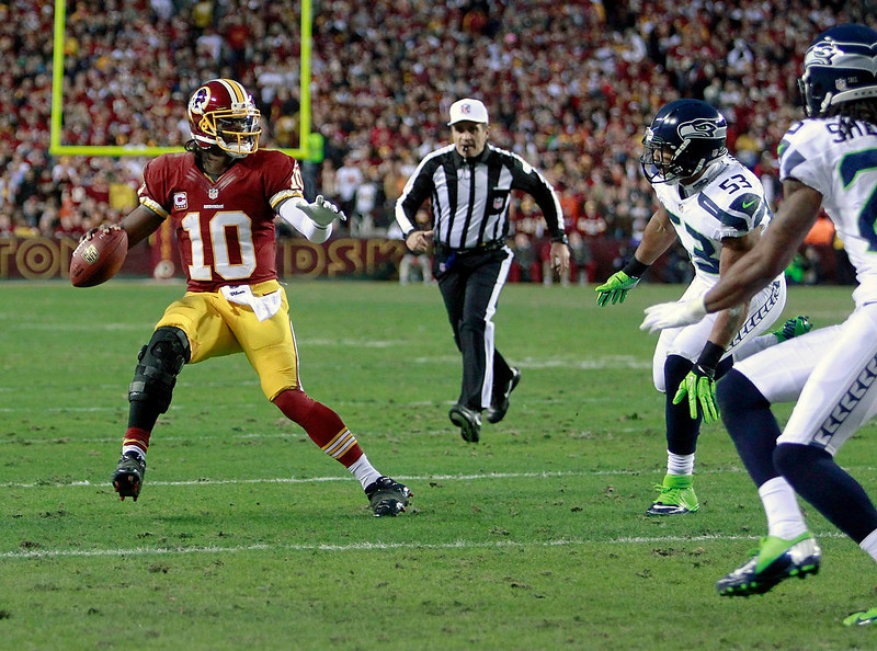 . Washington Redskins quarterback Robert Griffin III (L) under pressure from Seattle Seahawks outside linebacker Malcolm Smith (53) and cornerback Richard Sherman (R) during their NFL NFC wildcard playoff football game in Landover, Maryland, January 6, 2013. REUTERS/Tim Shaffer