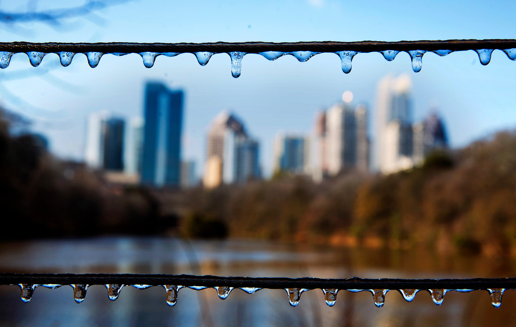. Ice covers a fence in Atlanta\'s Piedmont Park as the Midtown skyline stands in the background after a winter storm passed through on Saturday, Jan. 7, 2017. Snow and sleet pounded a large swath of the U.S. East Coast on Saturday, coating roads with ice and causing hundreds of crashes. In Atlanta and parts of Georgia, people who were expecting a couple of inches of snow instead woke up to a thin coat of ice. (AP Photo/David Goldman)