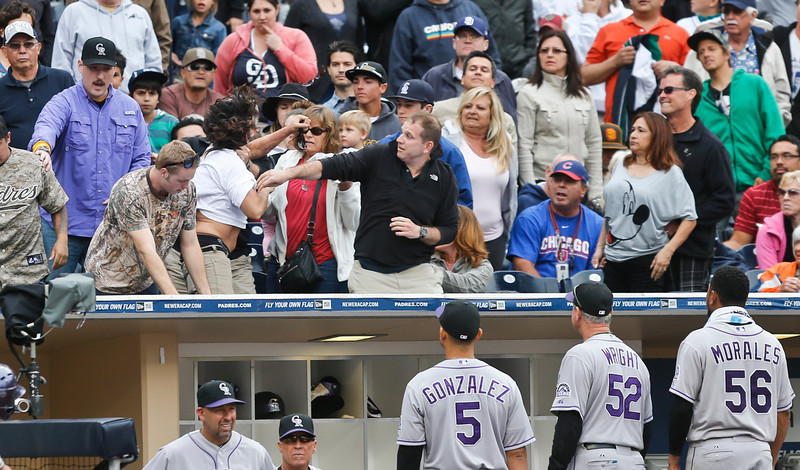 . Colorado Rockies players come out of the dugout as fans throw punches during a fight in stands that briefly delayed the baseball game against the San Diego Padres during the seventh inning Thursday, April 17, 2014, in San Diego. (AP Photo/Lenny Ignelzi)