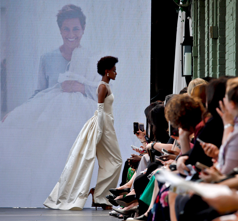 . An image of the late fashion designer Amsale Aberra fades onto a projection screen as a model, wearing the first-ever bridal gown she designed in 1990, exits the runway after the unveiling of the latest collection from Amsale during Bridal Fashion Week, Friday, April 13, 2018, in New York. (AP Photo/Bebeto Matthews)