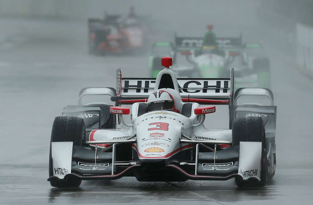 . Helio Castroneves, of Brazil, drives in the rain during the second race of the IndyCar Detroit Grand Prix auto racing doubleheader Sunday, May 31, 2015, in Detroit. (AP Photo/Paul Sancya)