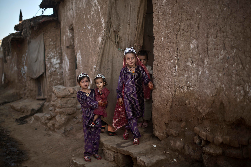 """. Afghan refugee girls dressed in new clothes, celebrate the first day of the Muslim holiday of Eid al-Adha, or \""""Feast of Sacrifice\"""", in a poor neighborhood on the outskirts of Islamabad, Pakistan, Wednesday, Oct. 16, 2013. (AP Photo/Muhammed Muheisen)"""