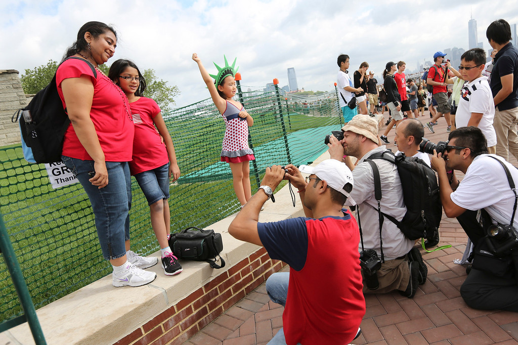 . Photographers take photos of people posing for pictures a the base of the Statue of Liberty, Thursday, July 4, 2013, in New York. The Statue of Liberty finally reopened on the Fourth of July months after Superstorm Sandy swamped Liberty Island in New York Harbor as Americans across the country marked the holiday with fireworks and barbecues. (AP Photo/Mary Altaffer)