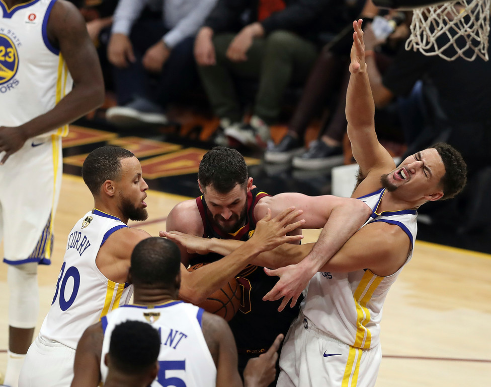 . Golden State Warriors guards Klay Thompson, right, and Stephen Curry (30) tie up Cleveland Cavaliers center Kevin Love during the first half of Game 3 of basketball\'s NBA Finals, Wednesday, June 6, 2018, in Cleveland. (AP Photo/Carlos Osorio)