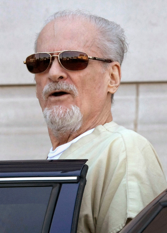 . FILE - In this July 23, 2009, file photo, Tony Alamo talks to reporters as he is escorted to a waiting police car outside the federal courthouse in Texarkana, Ark. Alamo, a one-time street preacher whose apocalyptic ministry grew into a multimillion-dollar network of businesses and property before he was convicted in Arkansas of sexually abusing girls he considered his wives, has died in prison Tuesday, May 2, 2017. He was 82. (AP Photo/Danny Johnston, File)