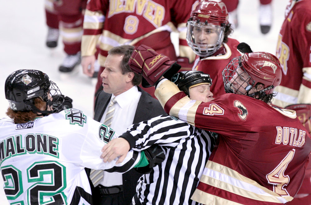 . Denver coach George Gwozdecky (center) goes onto the ice after fights break out at the end of the second period Saturday in Grand Forks. North Dakota forward Brad Malone and Denver defenseman Chris Butler are separated by a linesman.
