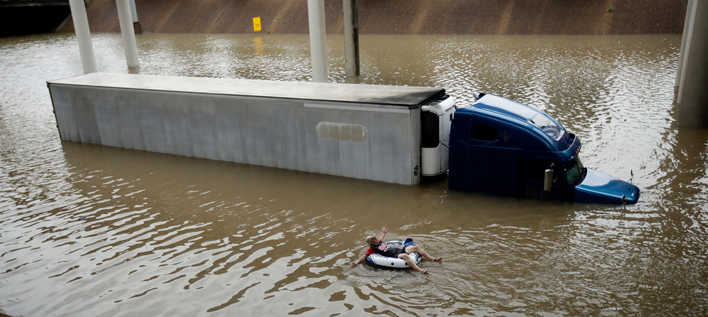 . After helping the driver of the submerged truck get to safety, a man floats on the freeway flooded by Tropical Storm Harvey on Sunday, Aug. 27, 2017, near downtown Houston.  (AP Photo/Charlie Riedel)