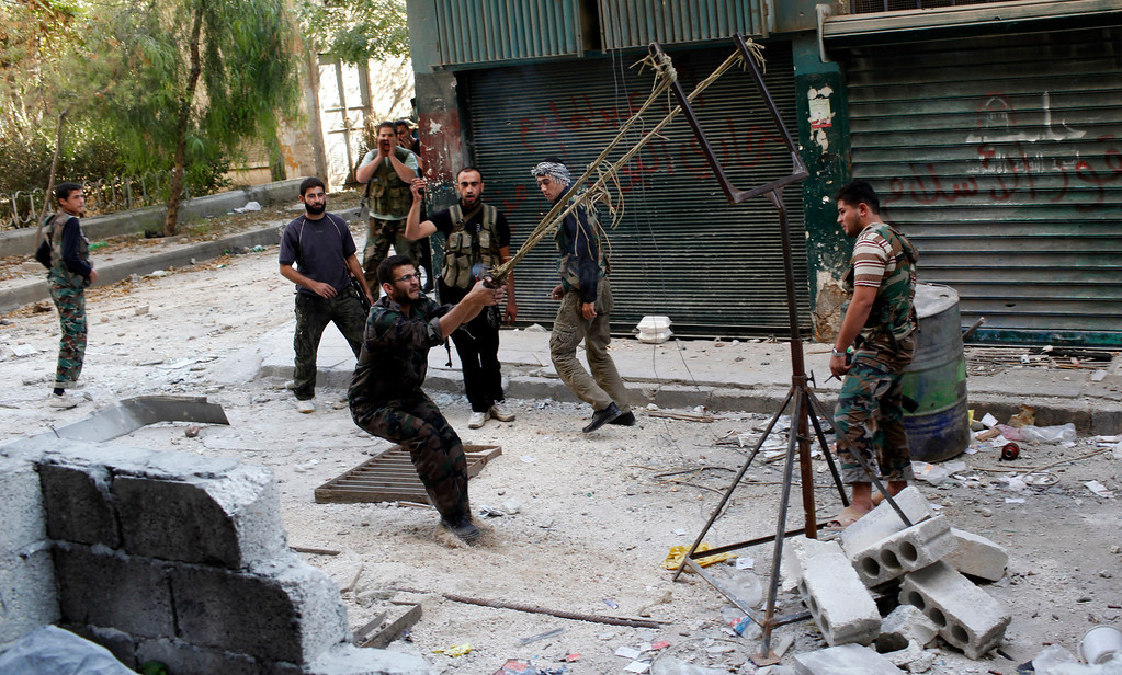 . Members of the free Syrian Army use a catapult to launch a homemade bomb during clashes with pro-government soldiers in the city of Aleppo, October, 15, 2012. REUTERS/Asmaa Waguih