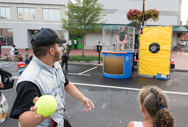 08/07/18 Wesley Bunnell | Staff New Britain Police held their annual National Night Out 2018 on Tuesday evening in a blocked off Central Park area. Marcos Martinez rears back ready to throw at the target on the dunk tank with CSO Julie Swan waiting to be dunked.