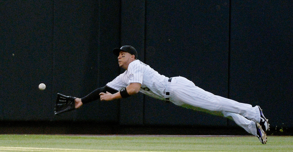 . Carlos Gonzalez (5) of the Colorado Rockies lays out trying to catch a fly ball hit by Gregor Blanco (7) of the San Francisco Giants during the third inning May 16, 2013 at Coors Field.  (Photo By John Leyba/The Denver Post)