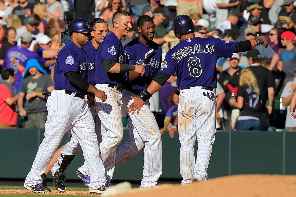 . Colorado Rockies\' Dexter Fowler, second from right celebrates his game-winning RBI-single during the bottom of the 10th inning of a baseball game against the Los Angeles Dodgers, Saturday June 1, 2013 in Denver. The hit scored Yorvit Torrealba (8) as the Rockies won 7-6. (AP Photo/Barry Gutierrez)