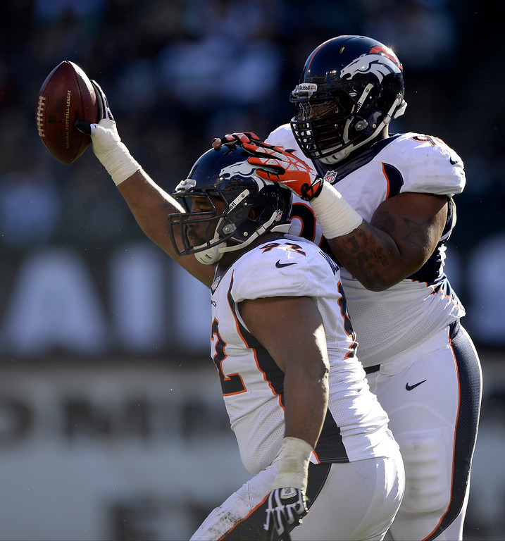 . Denver Broncos defensive tackle Sylvester Williams (92) hold sup the football after recovering a rumble by Oakland Raiders quarterback Terrelle Pryor (2) during the first quarter at O.co Coliseum. Denver Broncos defensive tackle Terrance Knighton (94) celebrates with him on the play. (Photo by John Leyba/The Denver Post)