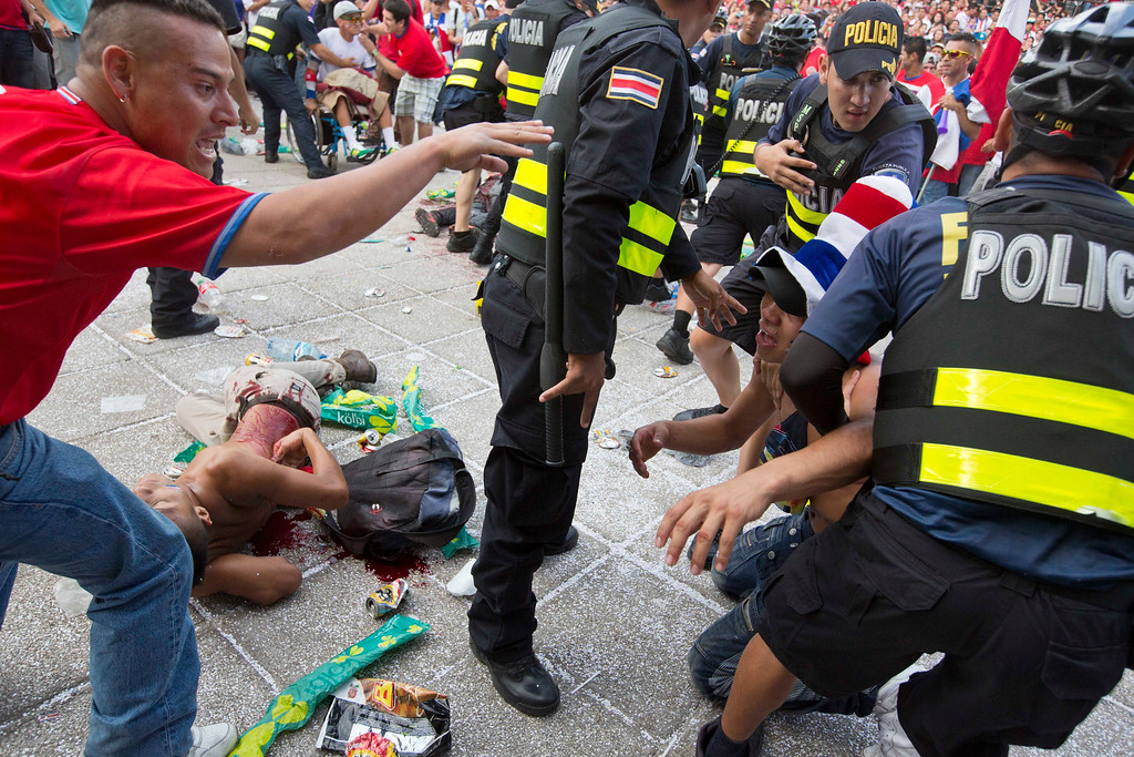 . A Costa Rica soccer fan is detained by the police while another fan lies on the ground injured with a knife, after a fight broke out during the live telecast of the quarterfinal World Cup match between Costa Rica and The Netherlands, at Democracy square in San Jose, Costa Rica, Saturday, July 5, 2014. Dutch Goalie Tim Krul came on as a substitute in the final minute of extra time and then saved two penalties in a 4-3 shootout victory over Costa Rica on Saturday, giving the Netherlands a spot in the World Cup semifinals. (AP Photo/Esteban Felix, File)