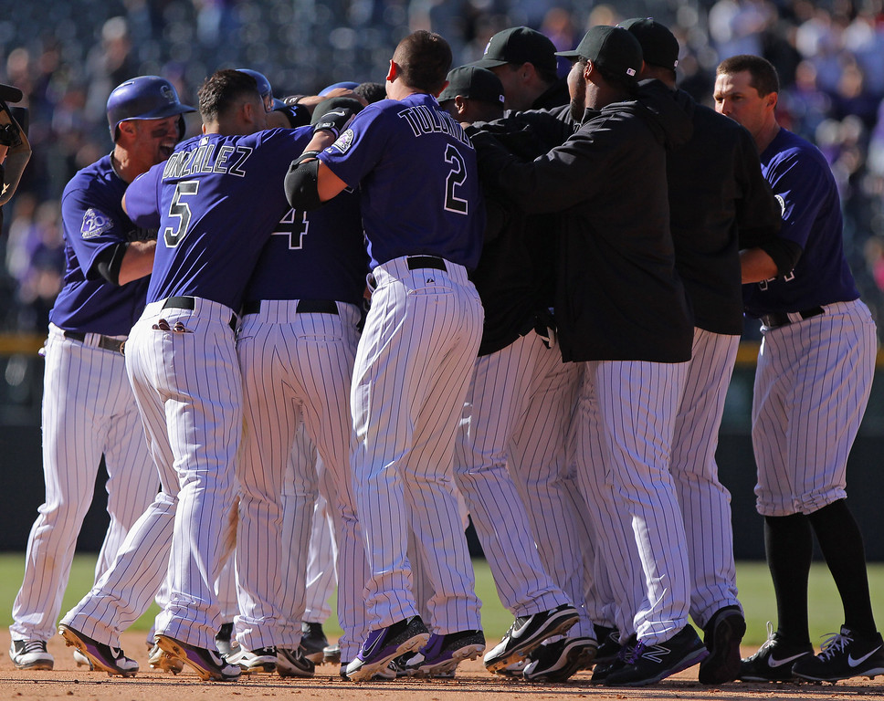 . The Colorado Rockies mob Yorvit Torrealba #8 of the Colorado Rockies to celebrate his game winning RBI single off of Luis Ayala #20 of the Atlanta Braves to score Wilin Rosario #20 of the Colorado Rockies in the bottom of the 12th inning at Coors Field on April 24, 2013 in Denver, Colorado. The Rockies defeated the Braves 6-5 in 12 innings.  (Photo by Doug Pensinger/Getty Images)