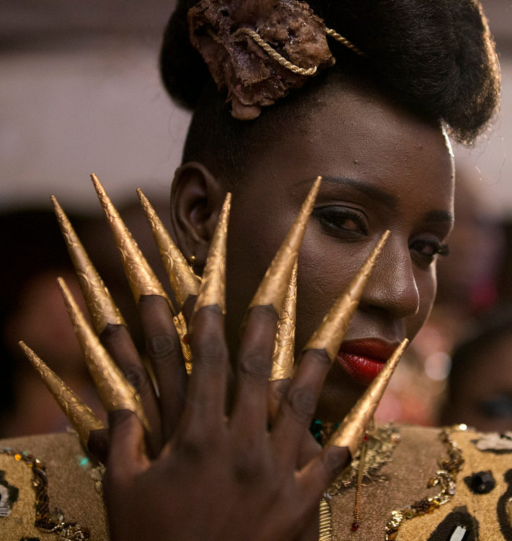 . A model wears a creation by Elie Kuame of Lebanon and Ivory Coast, as she waits backstage at Dakar Fashion Week, at Hotel des Almadies, in Dakar, Senegal, Saturday, June 22, 2013. After a Friday show held in a dusty marketplace in the working class suburb of Guediawaye, the runway finale of Dakar Fashion Week was held at a luxury hotel and showcased the work of 14 designers from West Africa, Europe, South America, and the Caribbean. (AP Photo/Rebecca Blackwell)