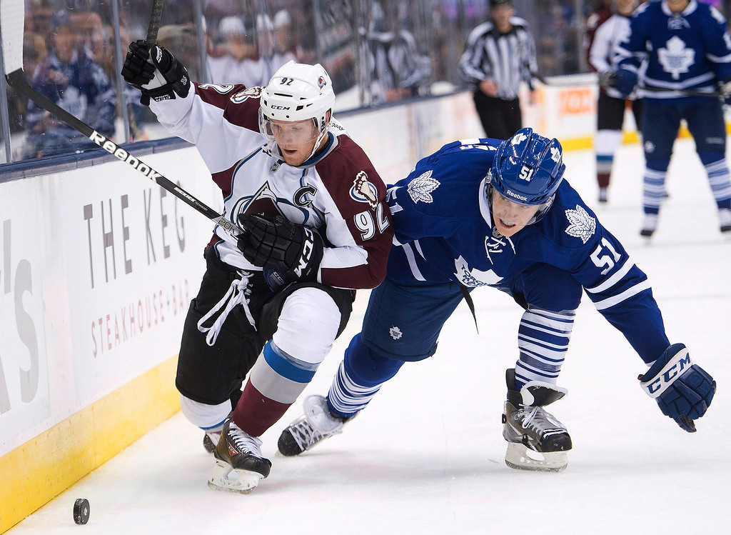 . Toronto Maple Leafs defenseman Jake Gardiner, right, and Colorado Avalanche forward Gabriel Landeskog, left, chase the puck after a check by Gardiner during the first period of an NHL hockey game in Toronto on Tuesday, Oct. 8, 2013. (AP Photo/The Canadian Press, Nathan Denette)