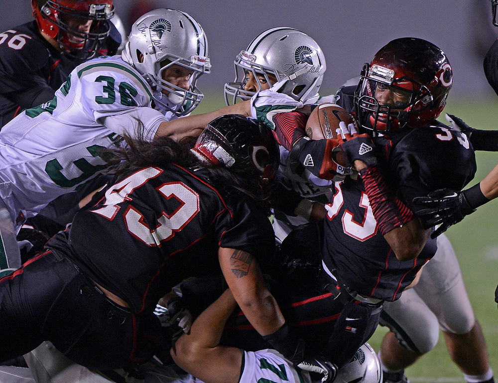 . Centennial Huskies\' John Plattenburg (33) gets tackled by De La Salle Spartans\' Kevin Koenig (76) in the first quarter of the Open Division during the 2012 CIF State Football Championship at Home Depot Center in Carson , Calif. on Saturday, Dec. 15, 2012. (Jose Carlos Fajardo/Staff)