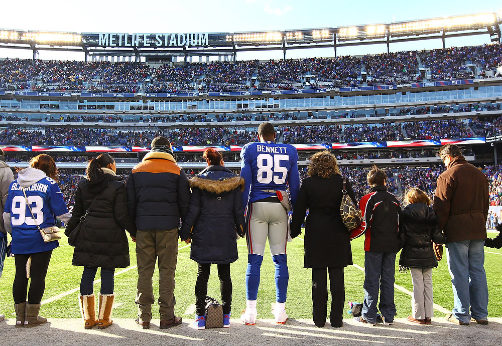 Description of . Martellus Bennett #85 of the New York Giants stands with  families of Sandy Hook Elementary School before the game against the Philadelphia Eagles  their game against the at MetLife Stadium on December 30, 2012 in East Rutherford, New Jersey.  (Photo by Al Bello/Getty Images)