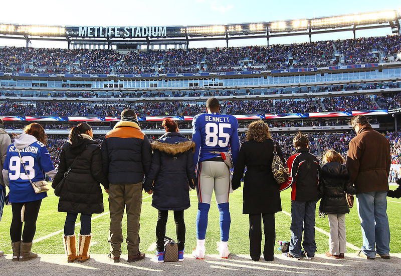 . Martellus Bennett #85 of the New York Giants stands with  families of Sandy Hook Elementary School before the game against the Philadelphia Eagles  their game against the at MetLife Stadium on December 30, 2012 in East Rutherford, New Jersey.  (Photo by Al Bello/Getty Images)