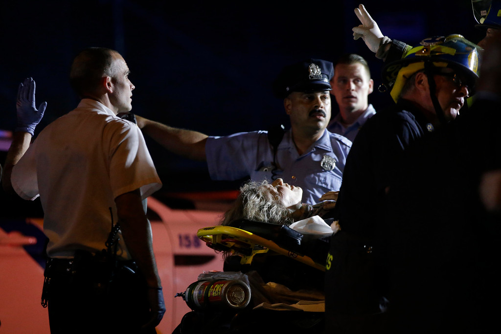 . Emergency personnel transport a person at the scene of a train wreck, Tuesday, May 12, 2015, in Philadelphia. An Amtrak train headed to New York City derailed and crashed in Philadelphia. (AP Photo/Matt Slocum)