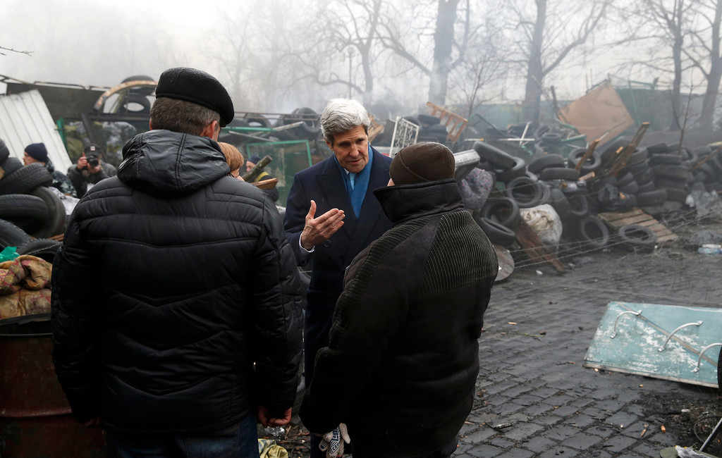 . Secretary of State John Kerry stands beside a barricade at the Shrine of the Fallen in Kiev, Ukraine, Tuesday, March 4, 2014.  (AP Photo/Kevin Lamarque, Pool)