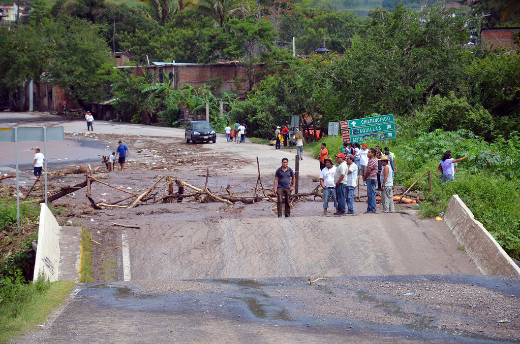 . People stand next to a collapsed bridge over the Huacapa River near the town of Petaquillas, Mexico, Tuesday, Sept. 17, 2013. Twin storms left scenes of havoc on both of Mexico\'s coasts on Tuesday, with tens of thousands of tourists stranded in resort city of Acapulco on the Pacific and heavy damage reported along the Gulf coast. (AP Photo/Alejandrino Gonzalez)