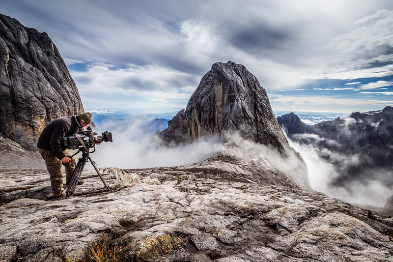 Cameraman Richard Kirby filming clouds building around Victoria Peak (4091 m), close to the summit of Mount Kinabalu, Borneo. For the BBC series Wonders of the Monsoon.