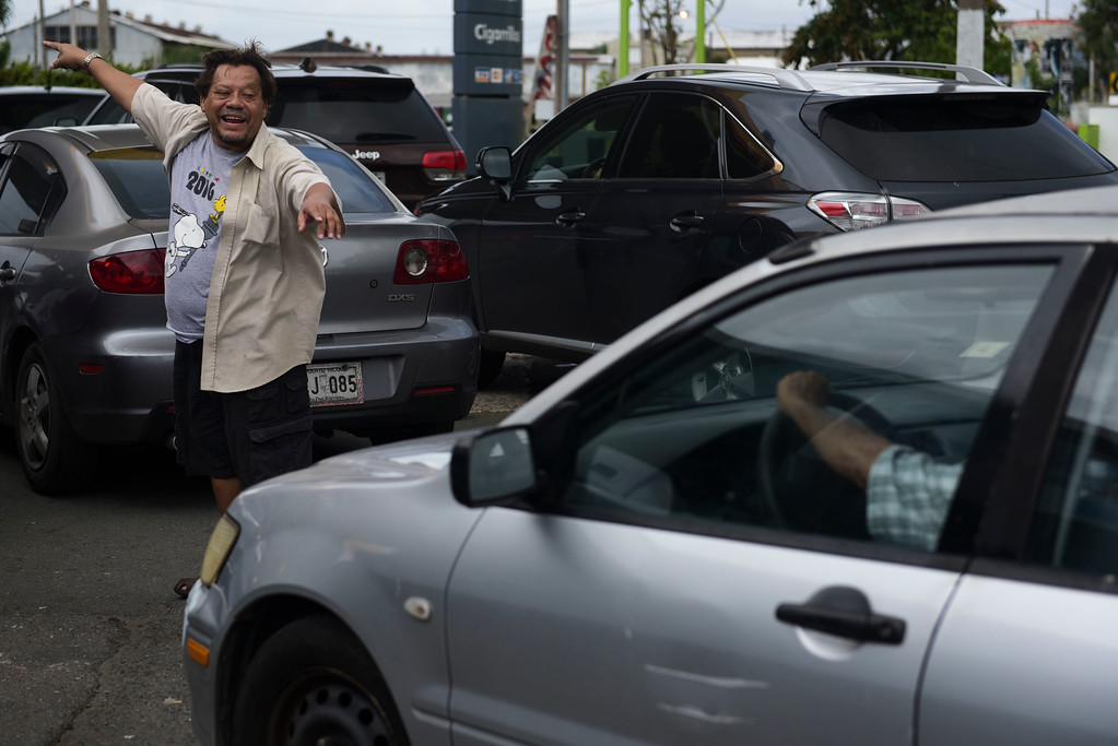 . CLIENTES EN PUERTO RICO:  POR FAVOR NO PUBLICAR ESTA FOTO. FUE A SUS SISTEMAS POR ERROR - A man directs drivers lining up to buy gasoline at a gas station one day before the forecasted arrival of Hurricane Maria in San Juan, Puerto Rico, Tuesday, Sept. 19, 2017. Authorities in the U.S. territory of Puerto Rico, which faces the possibility of a direct hit, warned that people in wooden or flimsy homes should find safe shelter before the storm�s expected arrival there on Wednesday. (AP Photo/Carlos Giusti)