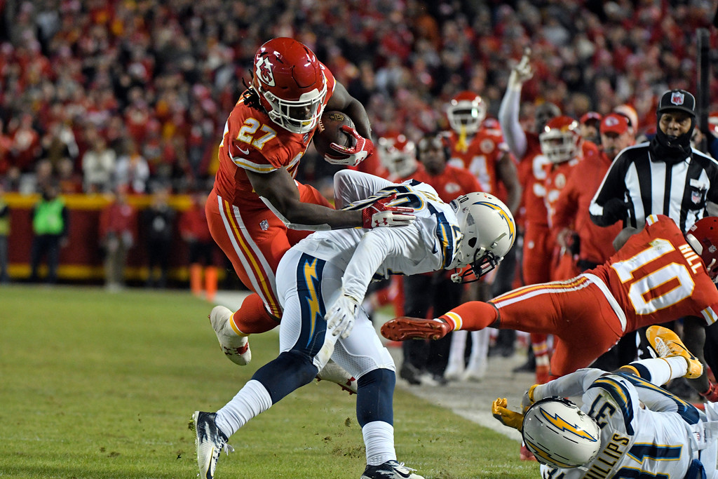 . Kansas City Chiefs running back Kareem Hunt (27) tries to get past Los Angeles Chargers defensive back Desmond King (20) during the first half of an NFL football game in Kansas City, Mo., Saturday, Dec. 16, 2017. (AP Photo/Ed Zurga)