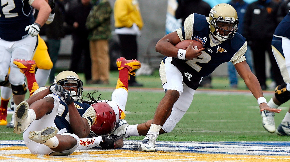 Description of . Georgia Tech quarterback Vad Lee is tripped up by a Southern California defender as he crosses the line of scrimmage during the Sun Bowl NCAA college football game, Monday, Dec. 31, 2012, in El Paso, Texas. (AP Photo/Mark Lambie)