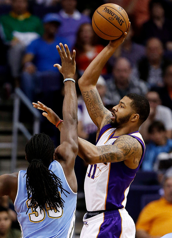 . Phoenix Suns\' Markieff Morris (11) shoots over Denver Nuggets\' Kenneth Faried during the first half of an NBA basketball game, Monday, March 11, 2013, in Phoenix. (AP Photo/Matt York)