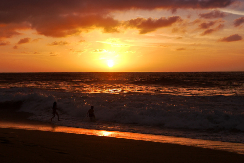 Children play in the surf as the sun sets in San Pancho, Mexico.