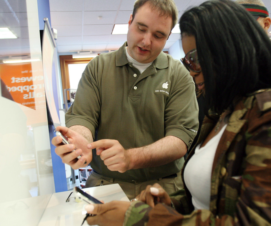 . Apple Solutions Consultant, Michael Grothaus, left, shows De Perkins, right, how the new iPhone works at the AT&T store in downtown Chicago, Friday, June 29, 2007. (AP Photo/ Stacie Freudenberg)