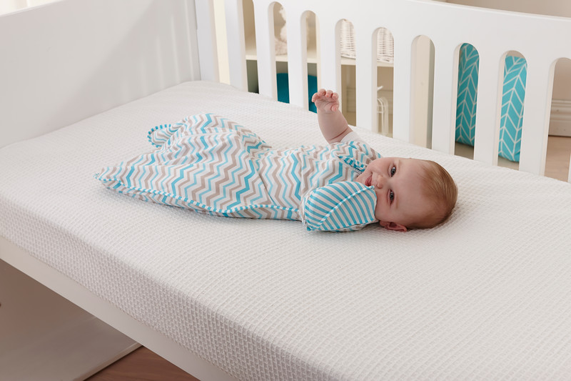 Love_To_Dream_Stage_2_5050_Zigzag_Turquoise_Lifestyle_View_In_Cot_Hand_In_Mouth.jpg