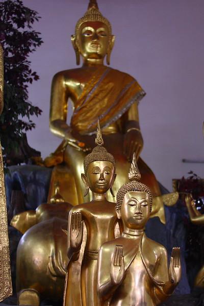 Three Buddhas with rear-end of elephant
