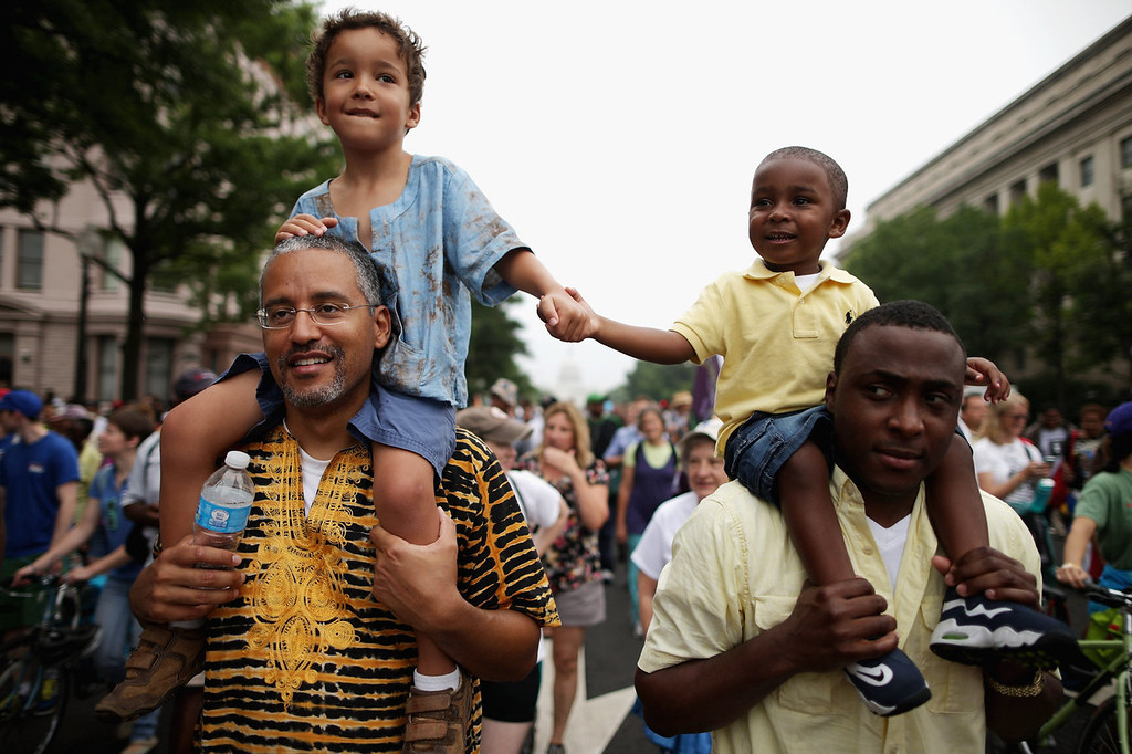 """. (L-R) John Mbugua and his son Giovanni Mbugua, 6, of San Jose, California, and Lavon Johnson and his son Mason Johnson, 2, of Fort Meade Maryland, hold hands while marching with thousands of other people from Capitol Hill to the Lincoln Memorial during the \'Let Freedom Ring Commemoration and Call to Action\' honoring the 50th anniversary of the historic March on Washington for Jobs and Freedom August 28, 2013 in Washington, DC. The 1963 landmark civil rights event was where Dr. Martin Luther King Jr. delivered his famous speech, saying, \'I still have a dream, a dream deeply rooted in the American dream...one day this nation will rise up and live up to its creed, \""""We hold these truths to be self evident: that all men are created equal.\"""" I have a dream . . .\'  (Photo by Chip Somodevilla/Getty Images)"""