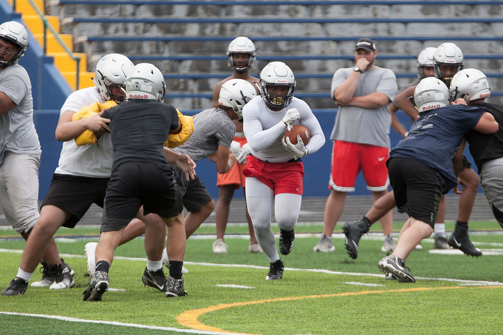 . Jen Forbus - The Morning Journal<br> Lorain\'s running back finds a hole to run through during Lorain\'s first football practice on July 30.
