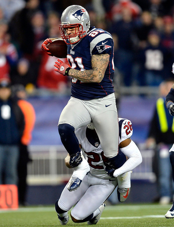 . New England Patriots tight end Aaron Hernandez (81) runs for a long gain deep into Houston Texans territory after catching a pass from quarterback Tom Brady during the third quarter of their NFL AFC Divisional playoff football game in Foxborough, Massachusetts January 13, 2013. The tackle is being made by Texans\' Brandon Harris.  REUTERS/Gretchen Ertl