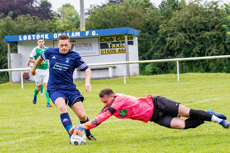 Lostock Gralam's Jack Wooley attempts to round the Northwich Victoria keeper