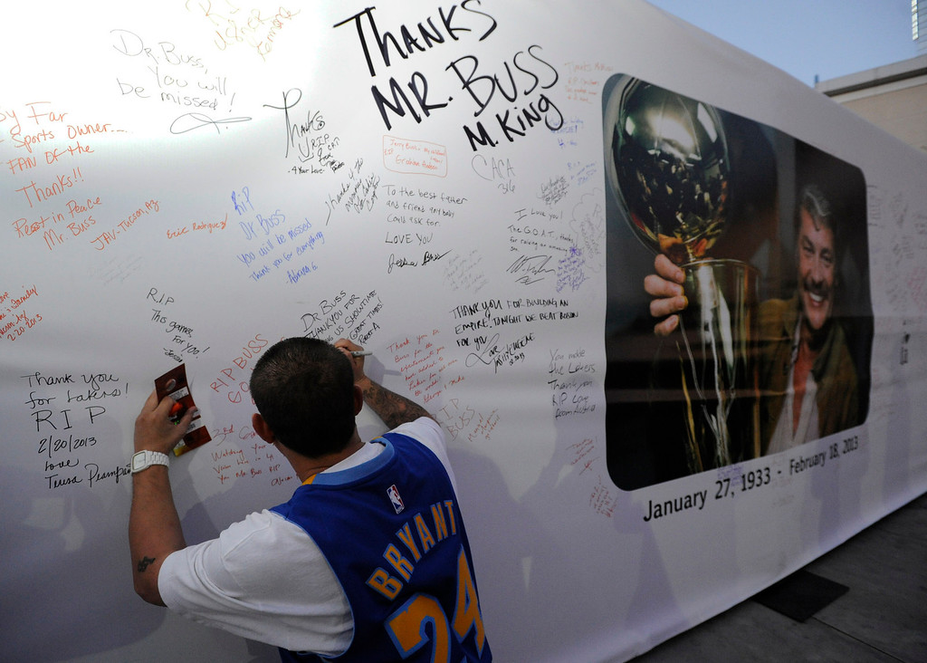 . Manuel Marquez writes his best wishes on a poster. The Lakers posted large banners around LA Live and Staples Center with a photo of Jerry Buss and plenty of room for fans to write their best wishes. Los Angeles, CA 2/20/2013(John McCoy/Staff Photographer)