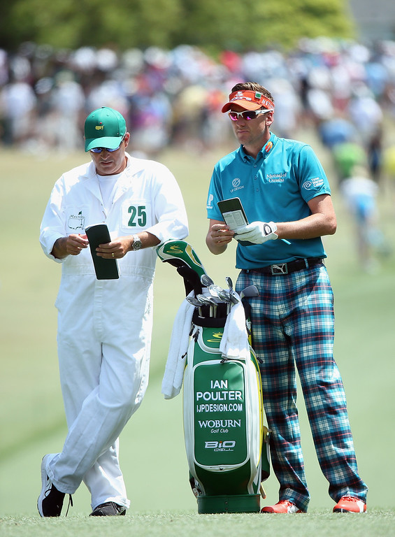 . Ian Poulter of England waits with his caddie Terry Mundy on the first hole during the final round of the 2014 Masters Tournament at Augusta National Golf Club on April 13, 2014 in Augusta, Georgia.  (Photo by Andrew Redington/Getty Images)