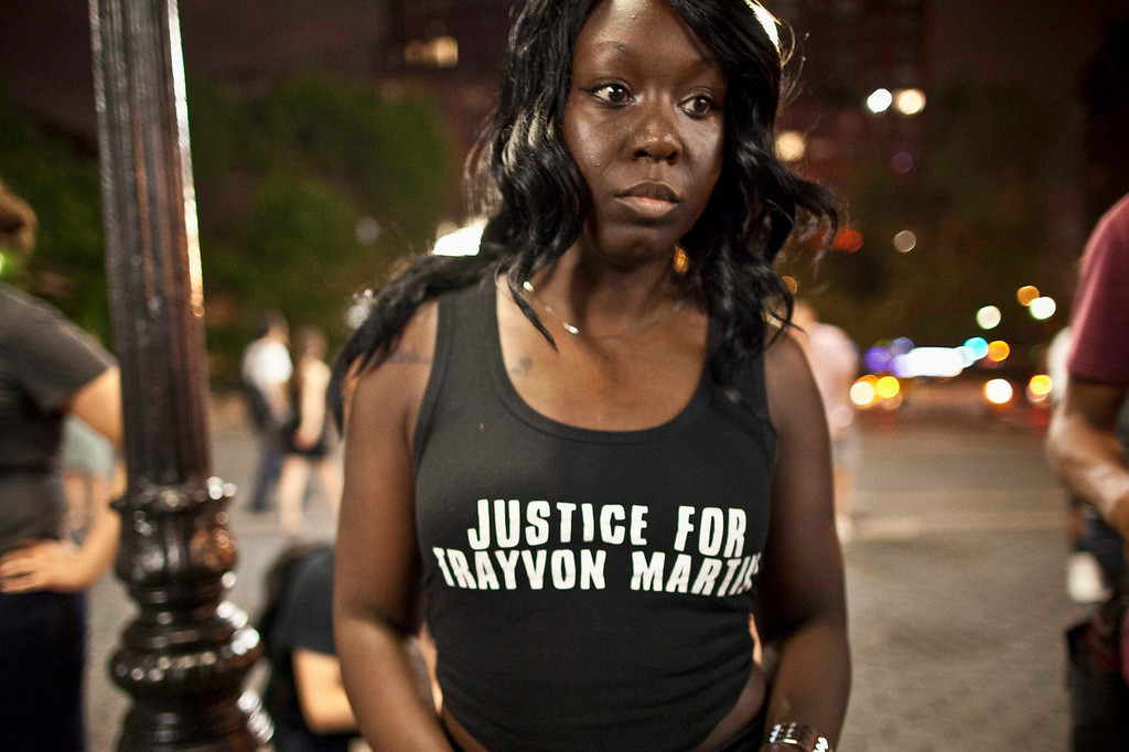 """. Brooklyn Nimoh of New York wears a \""""Justice For Trayvon Martin\"""" shirt as people gather at Union Square in response to the acquittal of George Zimmerman in the Trayvon Martin trial, in New York July 14, 2013. A Florida jury acquitted George Zimmerman on Saturday in the shooting death of unarmed black teenager Trayvon Martin in a case that sparked a national debate over racial profiling and self-defense laws. REUTERS/Andrew Kelly"""