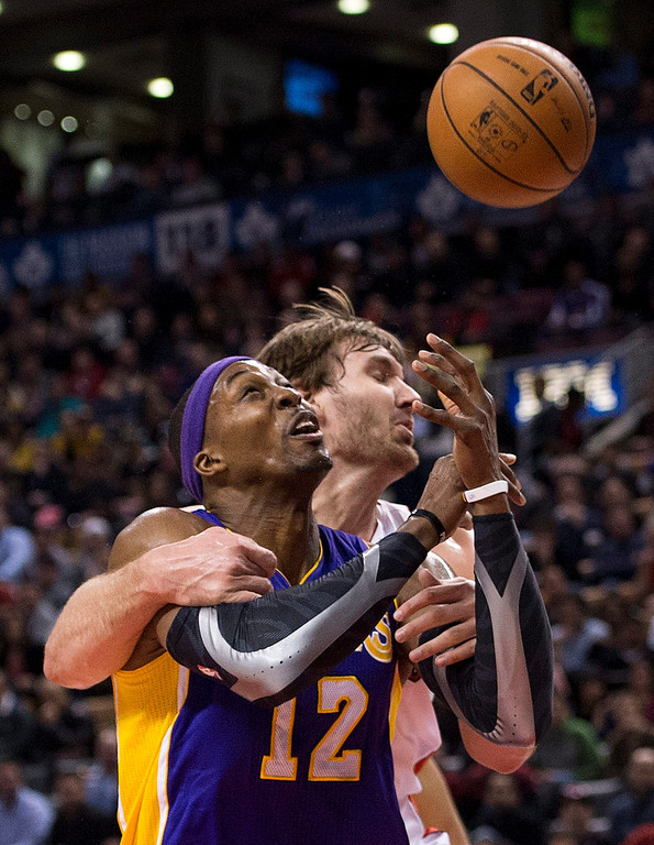 . Los Angeles Lakers forward Dwight Howard, left, drives past Aaron Gray, right, during first half NBA basketball action in Toronto on Sunday Jan. 20, 2013. (AP Photo/THE CANADIAN PRESS,Nathan Denette)