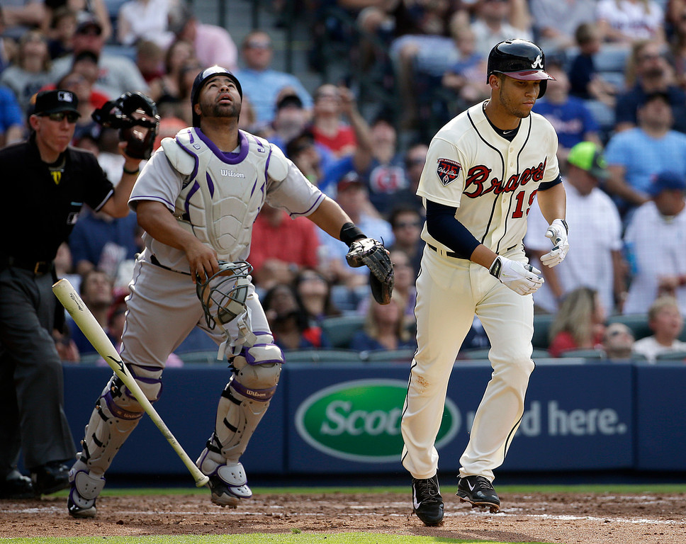 . Atlanta Braves\' Andrelton Simmons, right, tosses his bat after hitting a pop out as Colorado Rockies catcher Wilin Rosario, left, follows the ball in the fourth inning of a baseball game, Saturday, May 24, 2014, in Atlanta. (AP Photo/David Goldman)