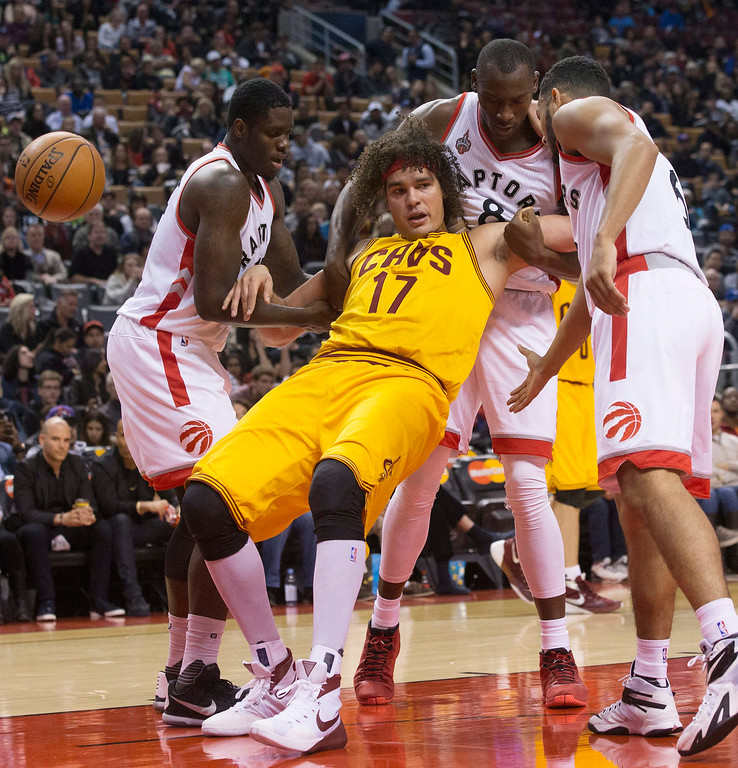 . Cleveland Cavaliers\' Anderson Varejao (17) is propped up by, from left to right, Toronto Raptors\' Anthony Bennett, Bismark Biyombo and Cory Joseph after being fouled during first-half preseason NBA basketball game action in Toronto, Sunday, Oct. 18, 2015. (Chris Young/The Canadian Press via AP)